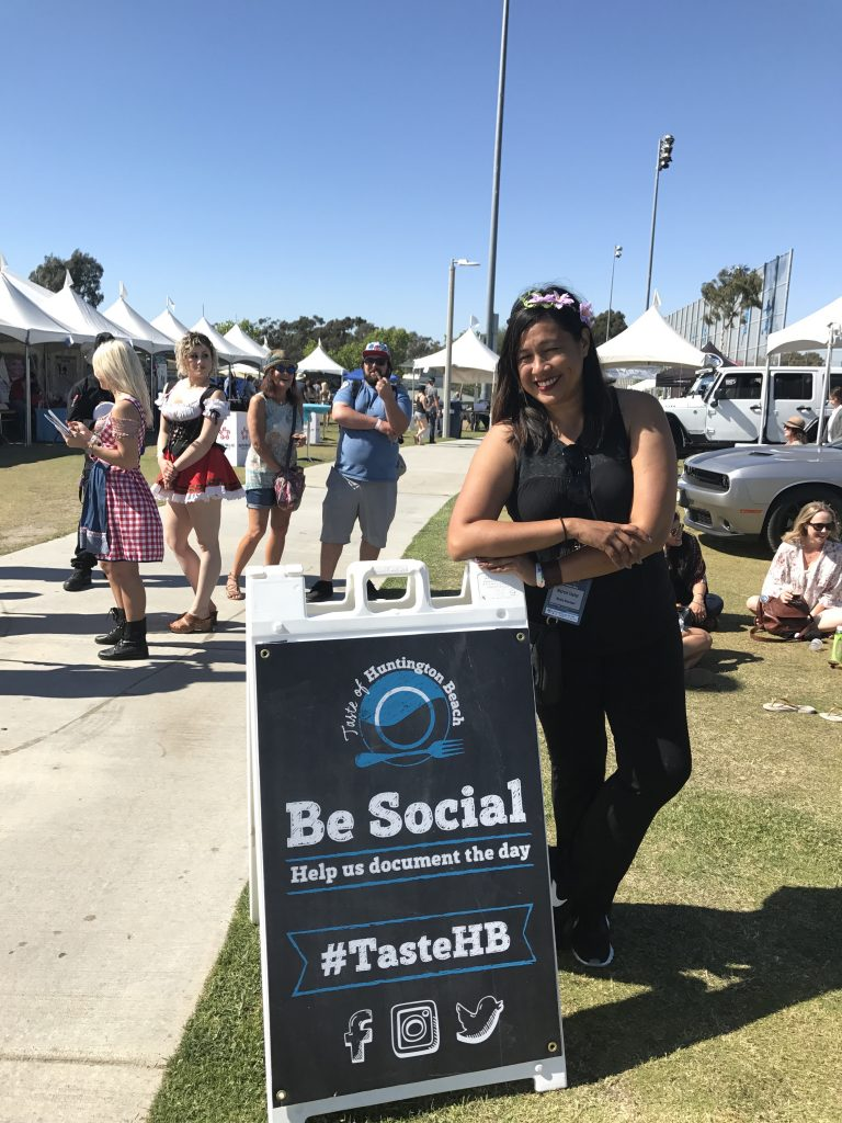 Marcie Taylor at Taste of Huntington Beach standing by social media sign